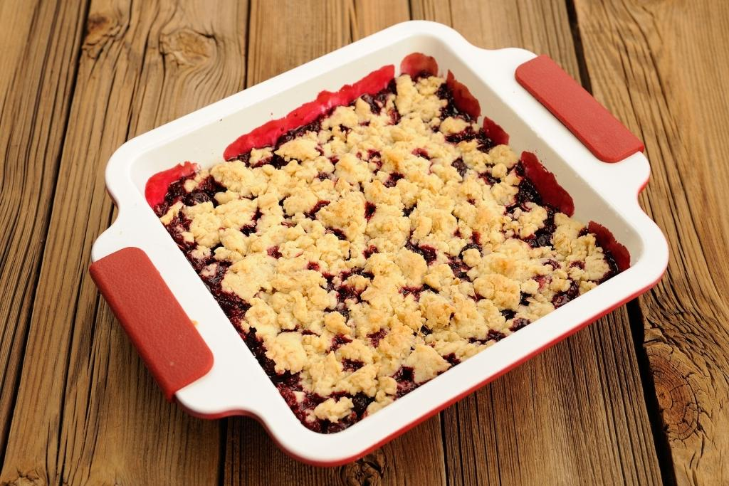 Tasty Homemade Cherry Oat Crumble In Square White Baking Dish On Wooden Table